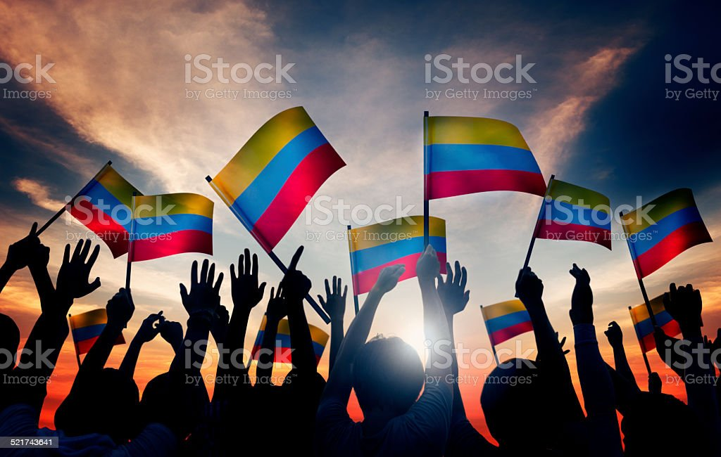 Group of People Waving Columbian Flags in Back Lit stock photo