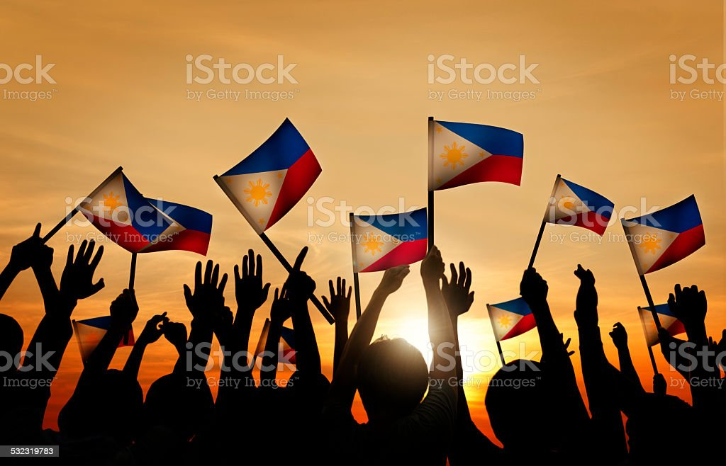 Group of People Waving Filipino Flags in Back Lit stock photo