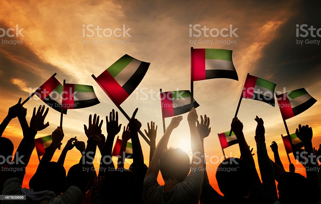 Group of People Waving Flag of UAE in Back Lit stock photo