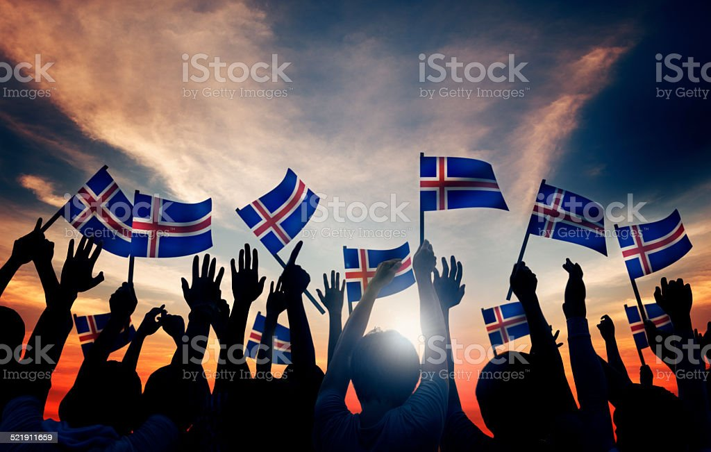 Group of People Waving Icelandic Flags in Back Lit stock photo