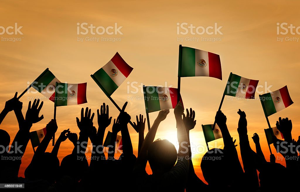 Group of People Waving Mexican Flags in Back Lit stock photo