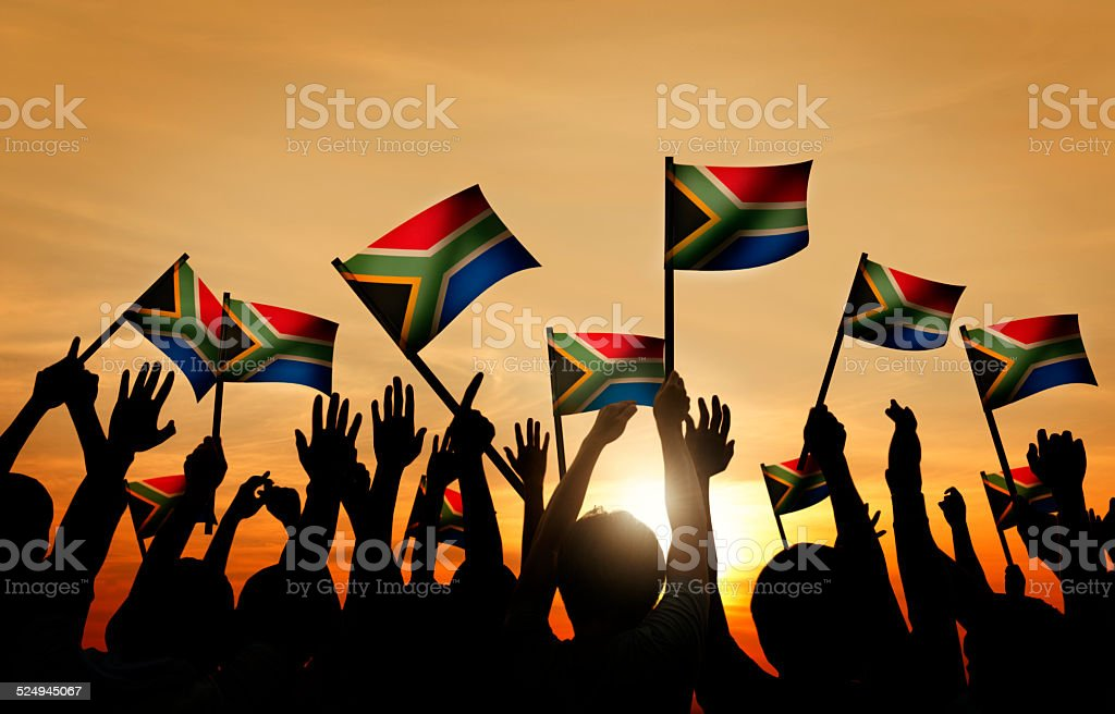 Group of People Waving South African Flags in Back Lit stock photo