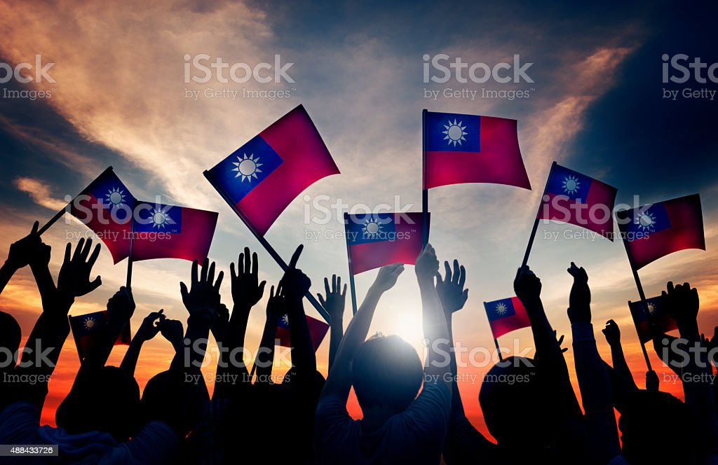Group of People Waving Taiwanese Flags in Back Lit stock photo