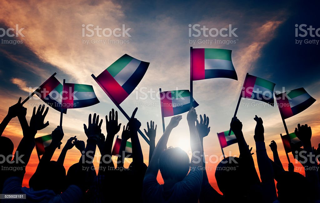 Group of People Waving the Flag of UAE stock photo