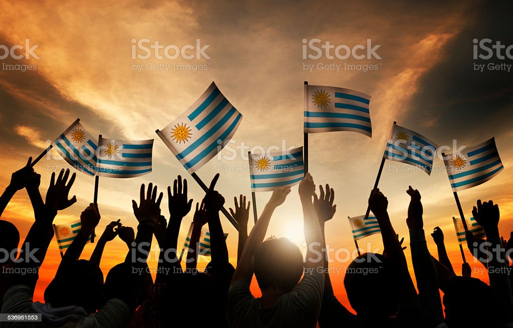 Group of People Waving Uruguayan Flags in Back Lit stock photo