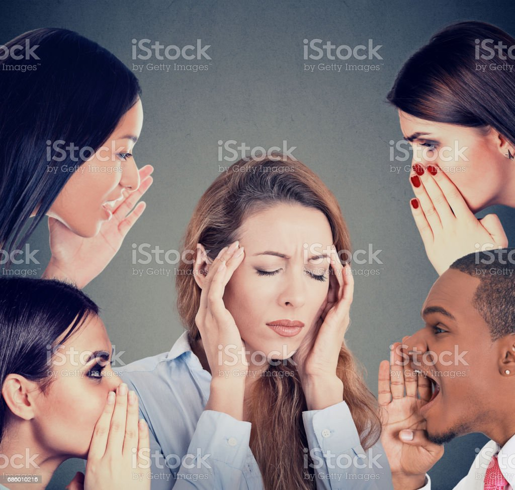 Group of people whispering gossip to a stressed woman suffering from headache stock photo