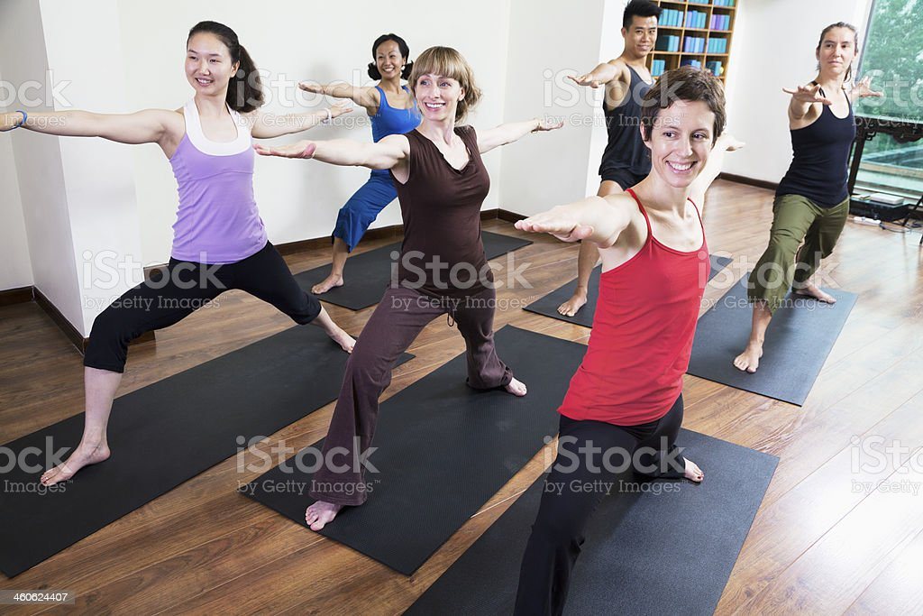 Group of people with arms outstretched doing yoga stock photo