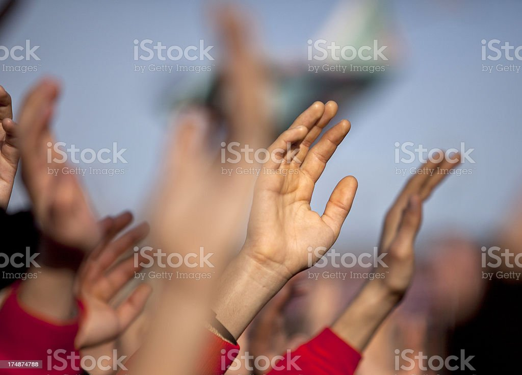 Group of people with arms raised above stock photo