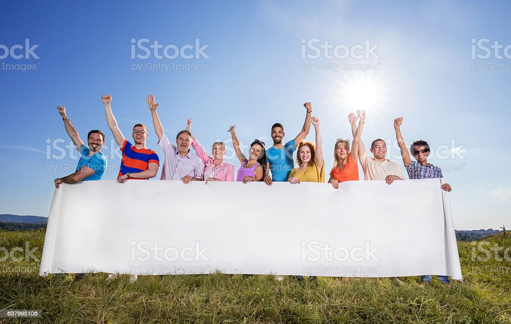 Group of people with arms raised holding blank banner outdoors. stock photo
