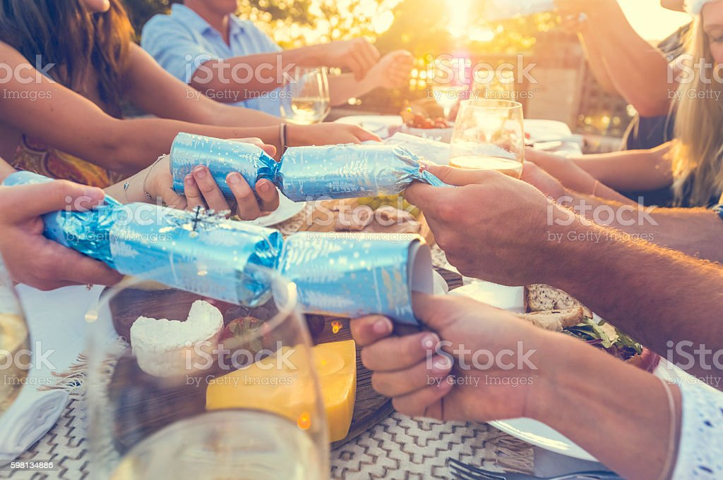 Group of people with Christmas crackers. stock photo