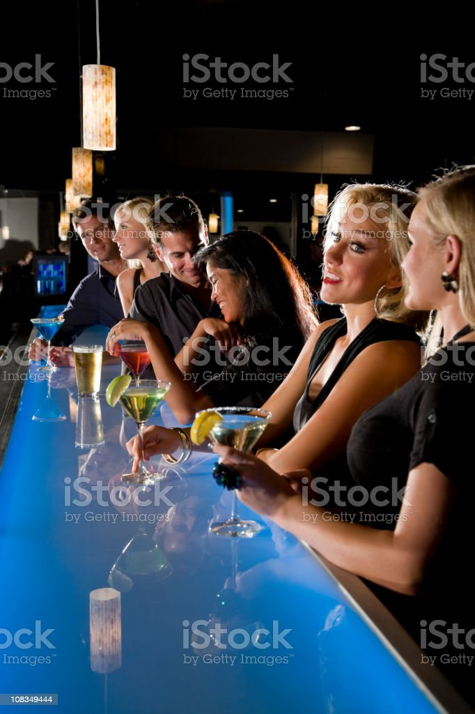 Group of people with drinks at nightclub bar stock photo