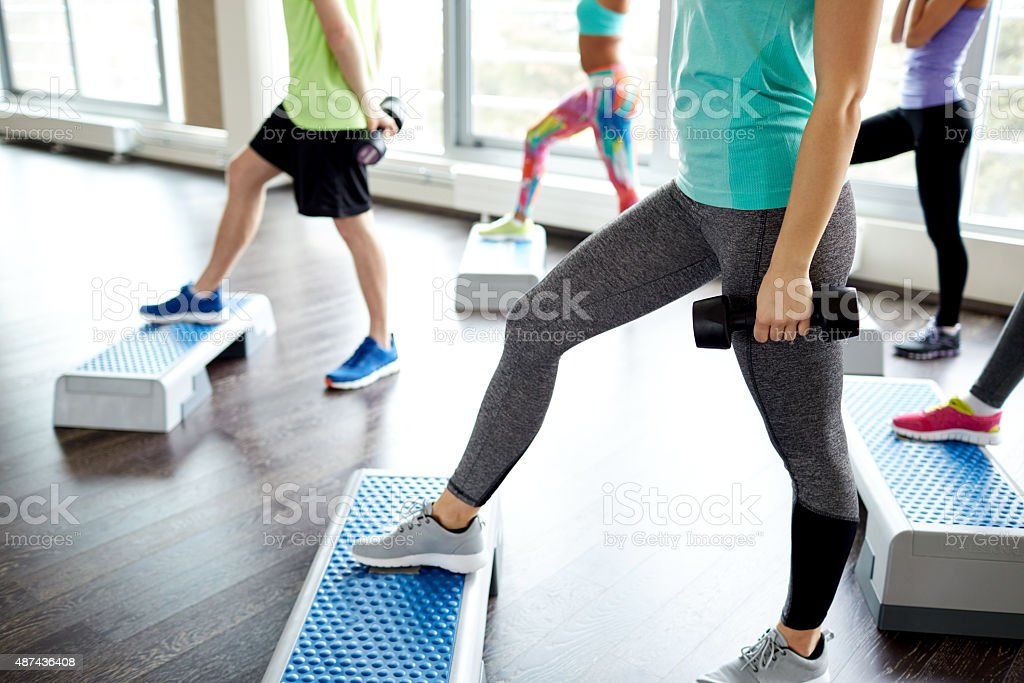 group of people with dumbbells and steppers stock photo