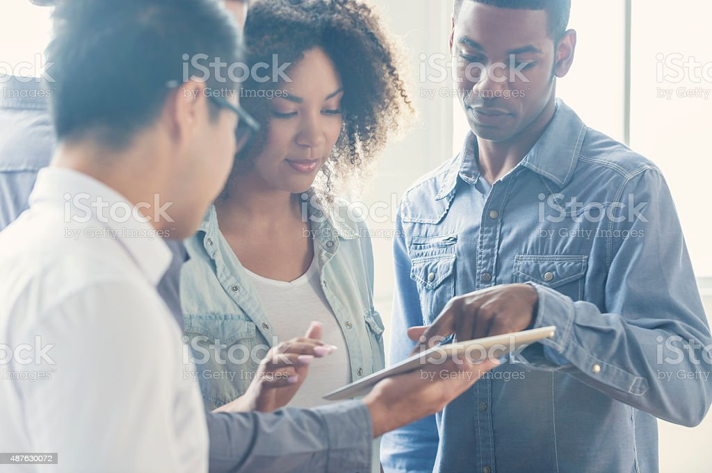 Group of people working on digital tablet in an office. stock photo