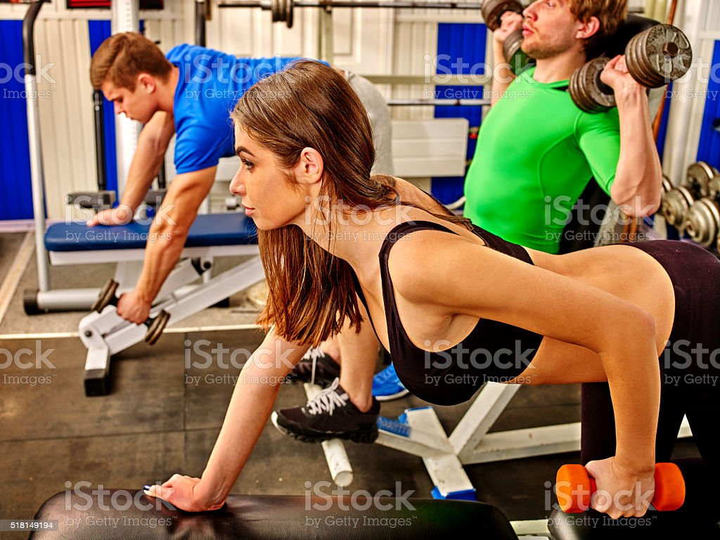 Group of people  working with dumbbells  at gym stock photo
