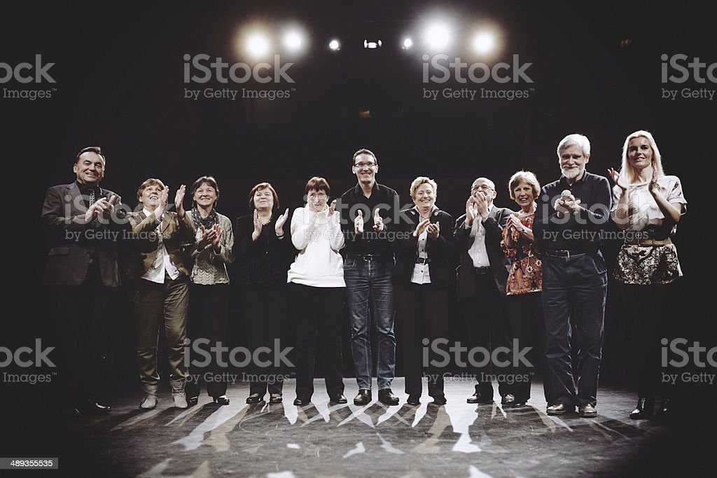 group of performers on stage clapping stock photo