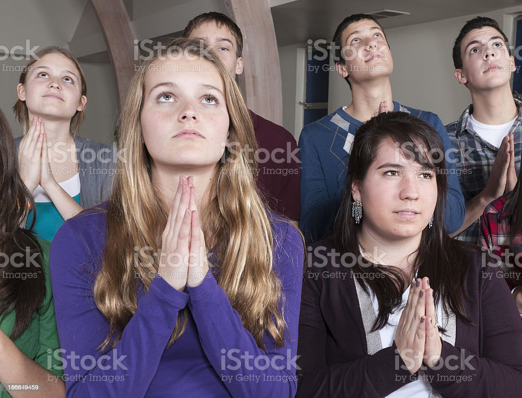 Group of Praying Teens, Eyes Looking Up royalty-free stock photo