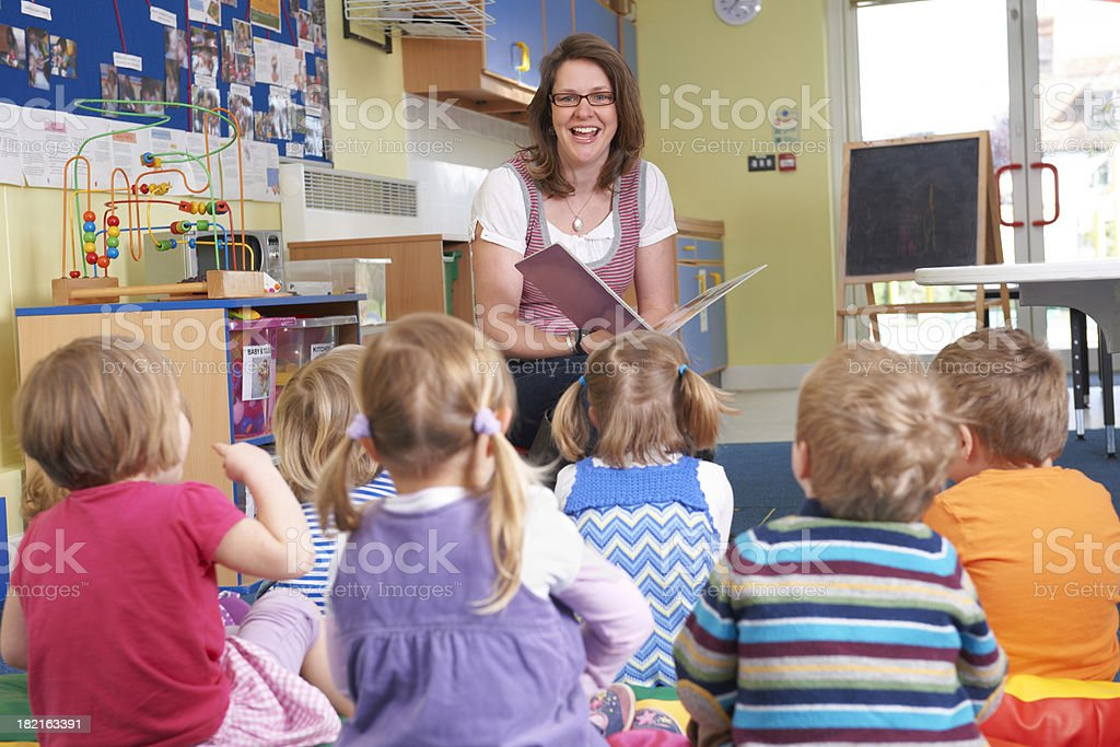 Group Of Pre School Children Listening To Teacher Reading Story stock photo