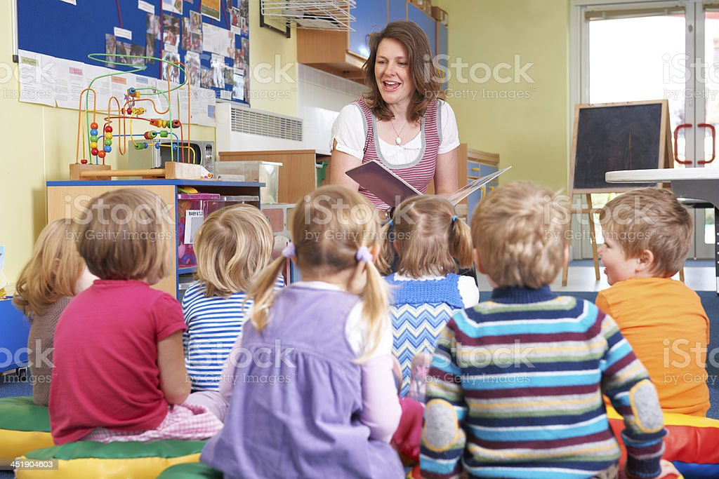 Group Of Pre School Children Listening To Teacher Reading Story royalty-free stock photo