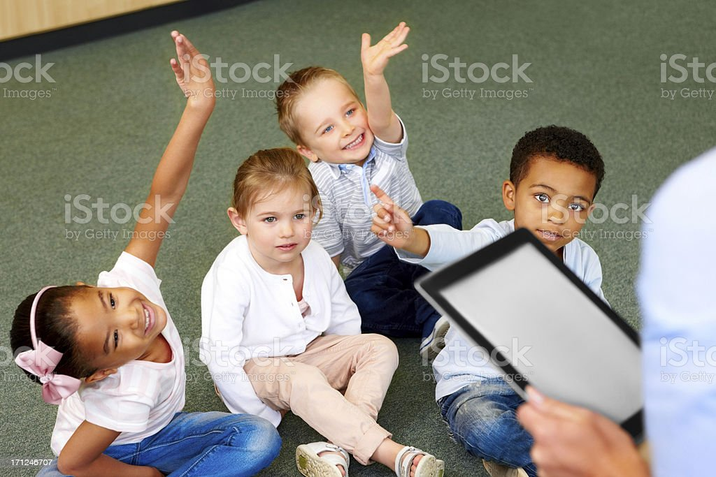 Group of preschool kids in classroom raising hands royalty-free stock photo