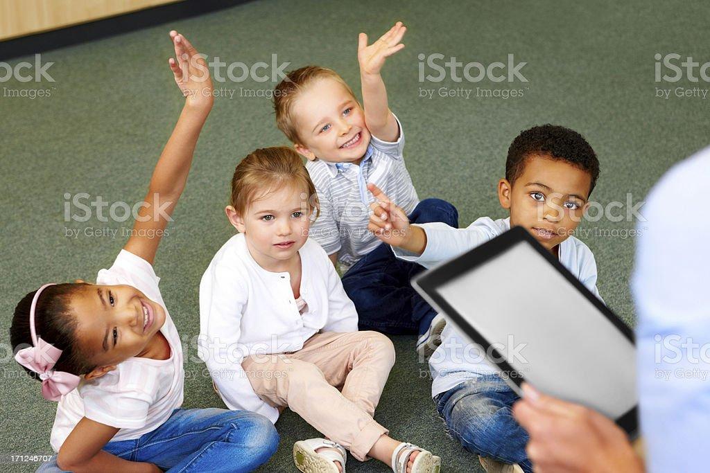 Group of preschool kids in classroom raising hands stock photo