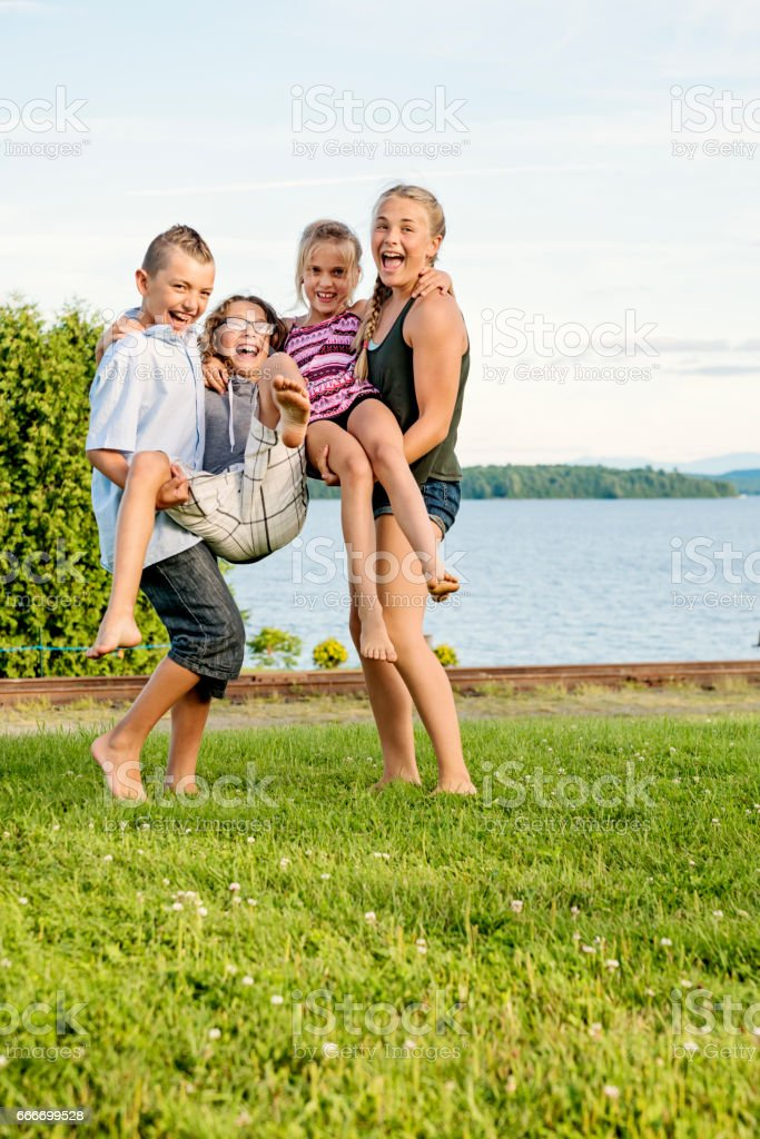 Group of preteen children playing front of lake in summer. stock photo