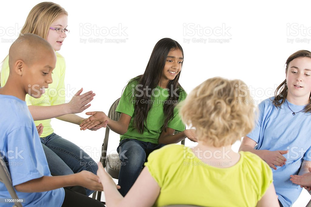 Group of pre-teens children playing a game in circle royalty-free stock photo