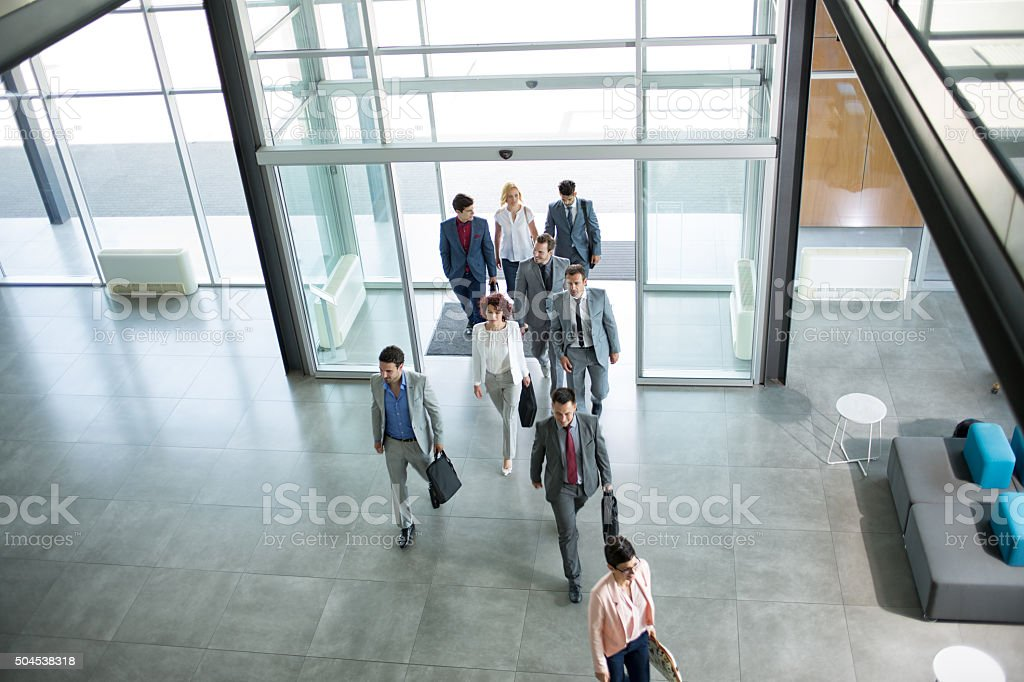 Group of professional business people walking in building stock photo