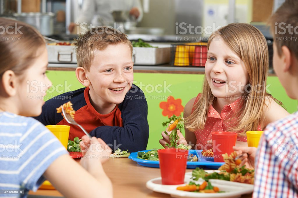 Group Of Pupils In School Cafeteria Eating Lunch stock photo