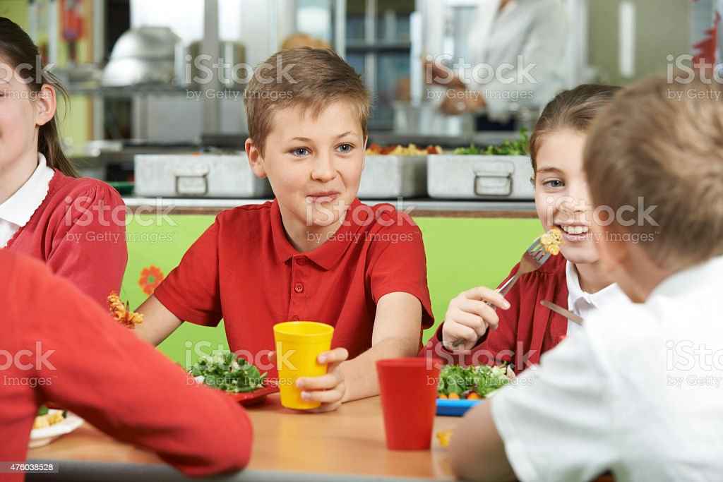 Group Of Pupils Sitting At Table In School Cafeteria stock photo