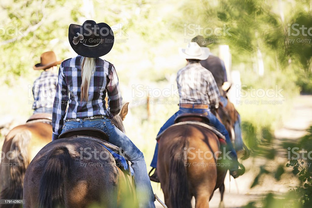 Group of ranchers riding horses together outdoors at ranch stock photo