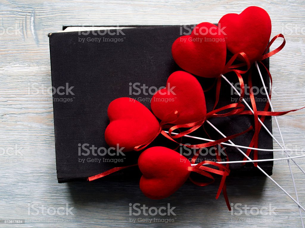 Group of red heart lie on old black book. stock photo