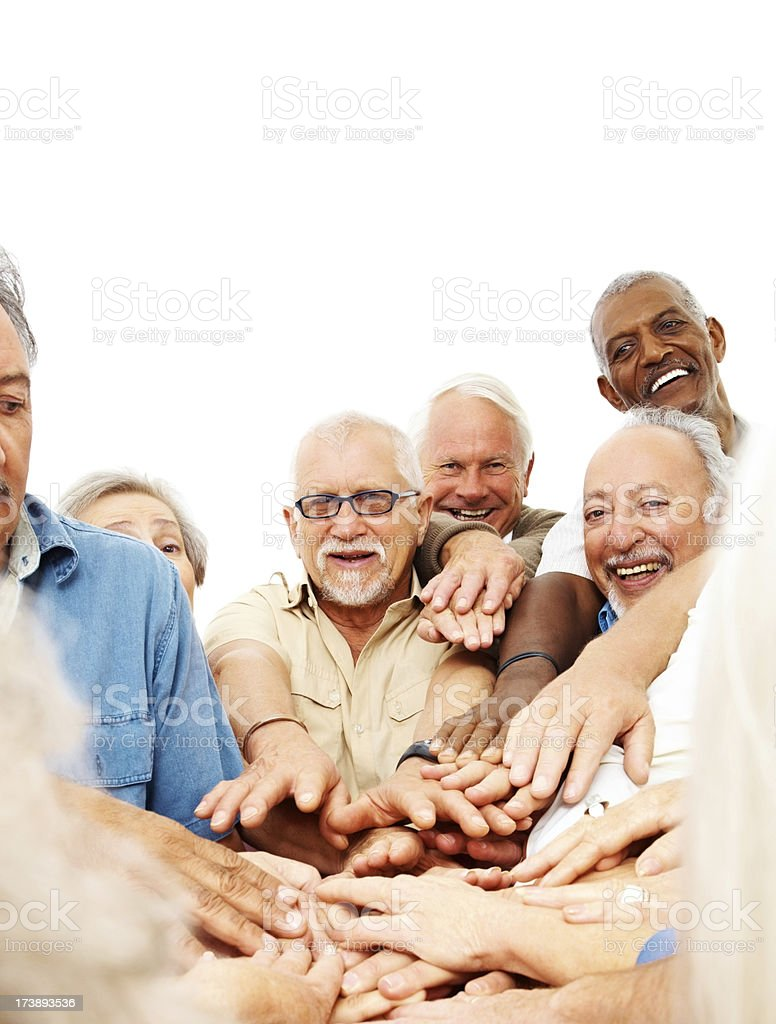 Group of retired people putting their hands together royalty-free stock photo