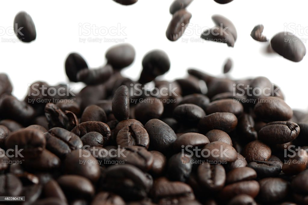Group of roasted coffee beans and falling seed stock photo