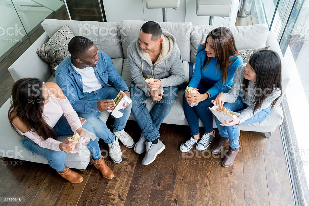 Group of roommates having dinner at home stock photo