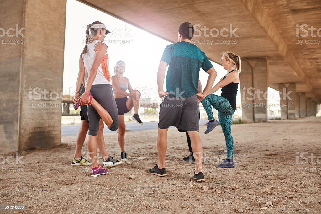 Group of runners stretching stock photo