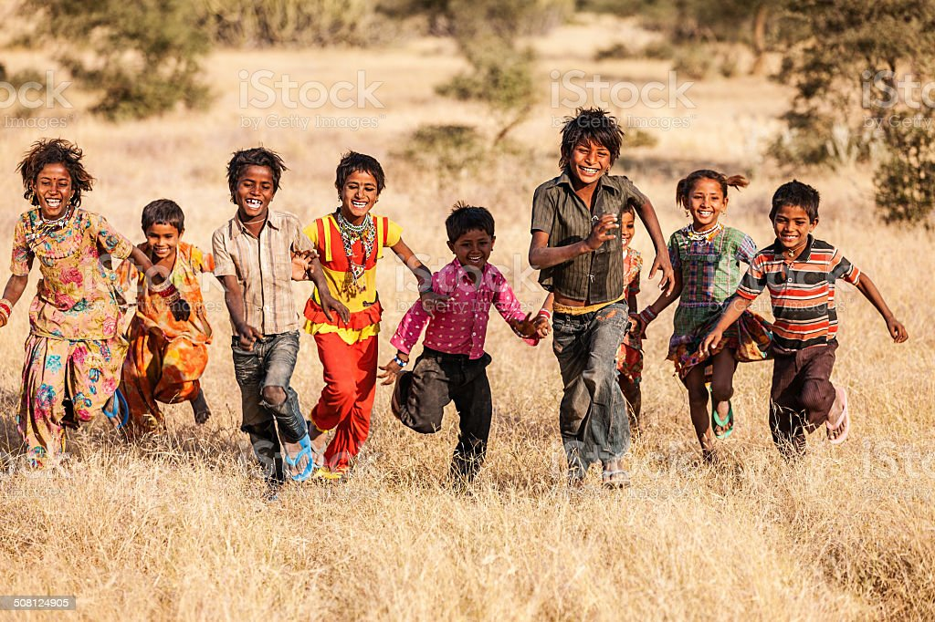 Group of running happy Indian children, desert village, India stock photo
