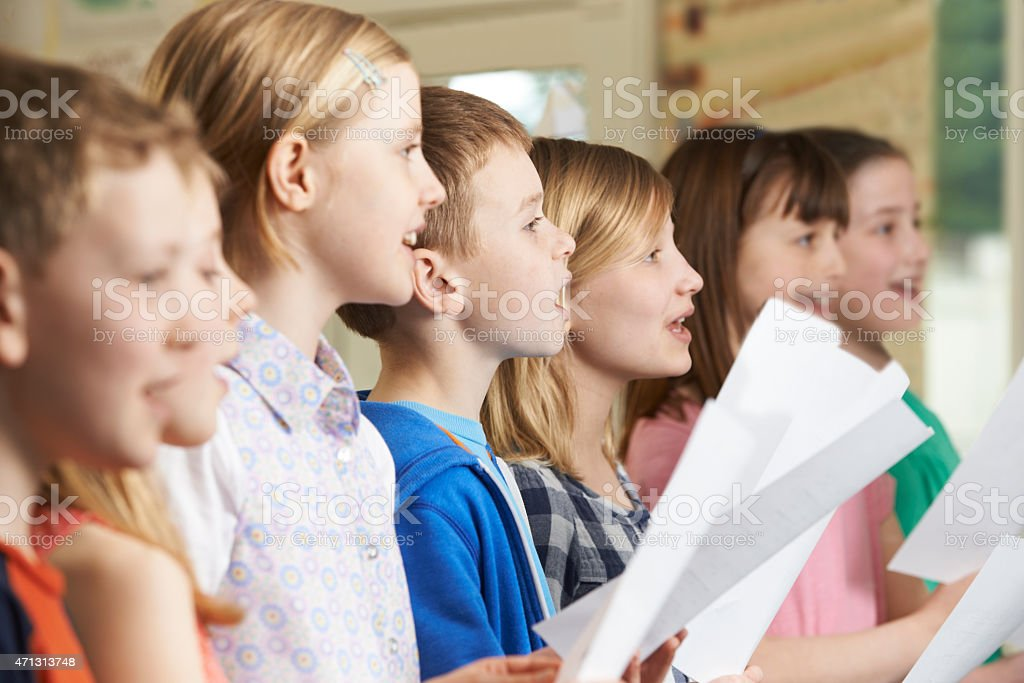 Group Of School Children Singing In School Choir stock photo