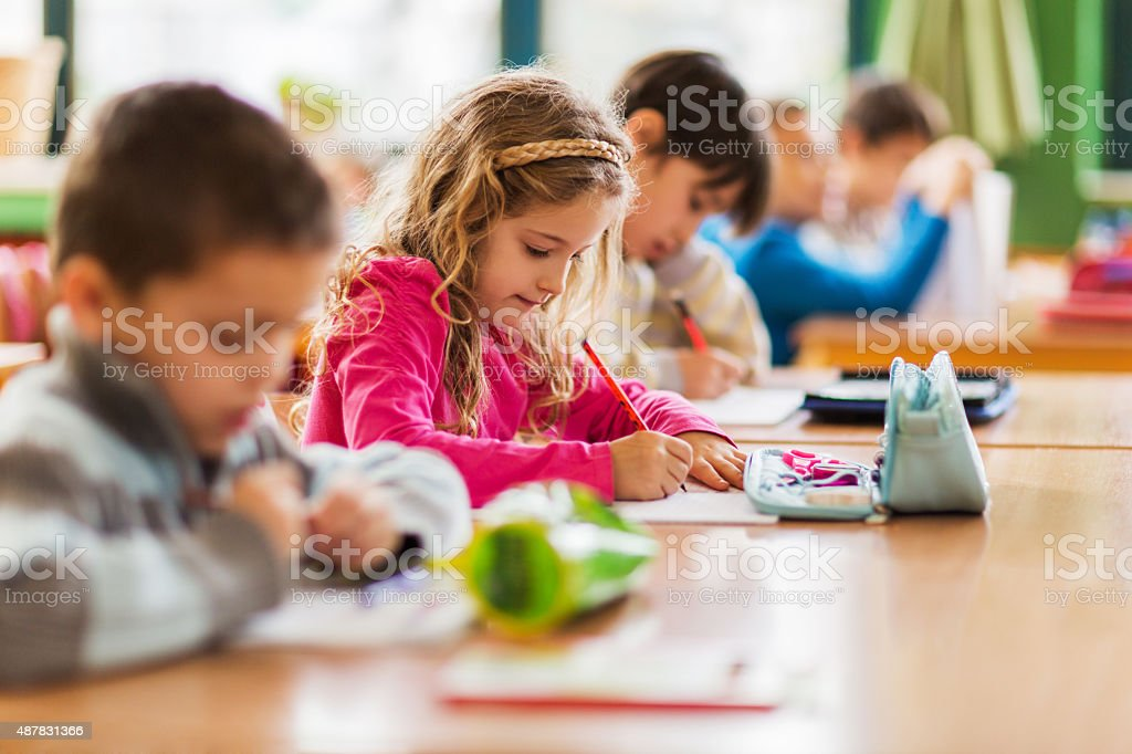 Group of school children sitting in the classroom and writing. stock photo