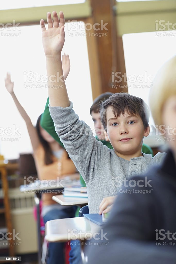 Group of school children with hands raised in a classroom royalty-free stock photo