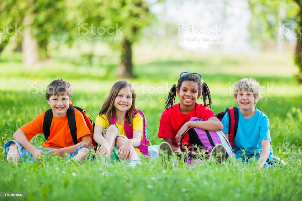 Group of school kids sitting in park. stock photo