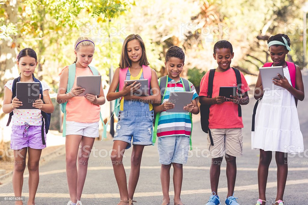 Group of school kids using digital tablet stock photo