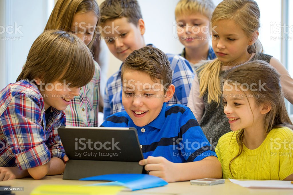 group of school kids with tablet pc in classroom stock photo