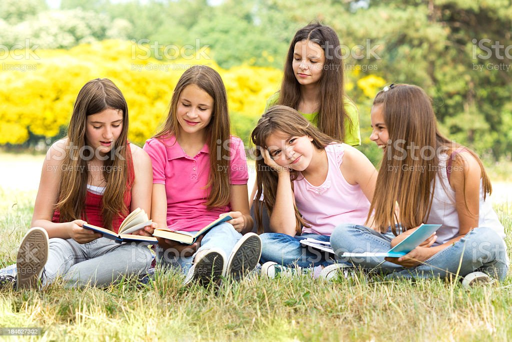 Group Of Schoolgirls Reading Books Outdoors royalty-free stock photo