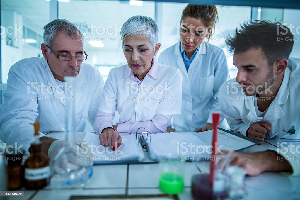 Group of scientists reading scientific data in the laboratory. stock photo