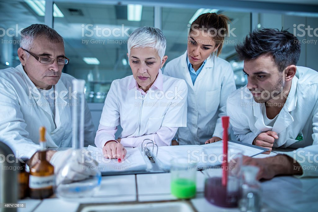 Group of scientists reading scientific research in the laboratory. stock photo