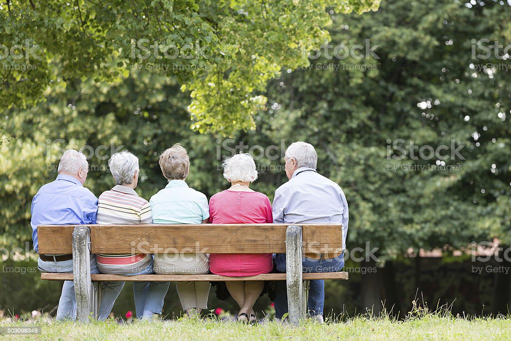 Group of senior adult on bench in the park stock photo