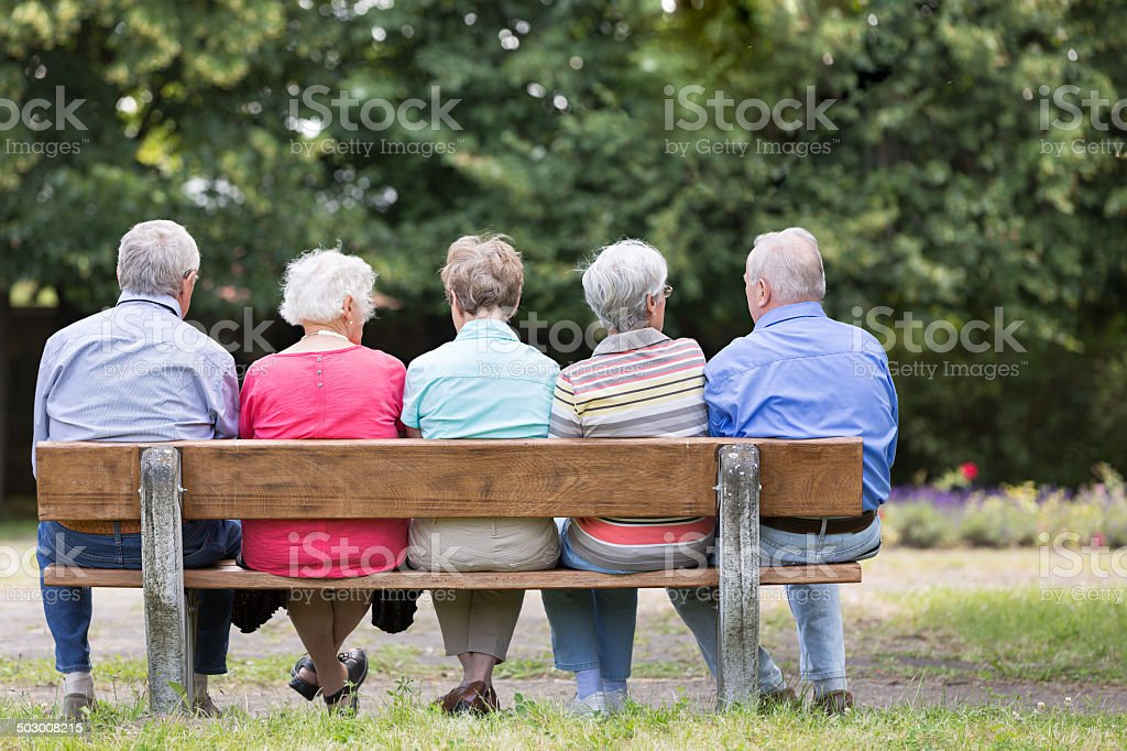 Group of senior adult on park bench outdoors stock photo