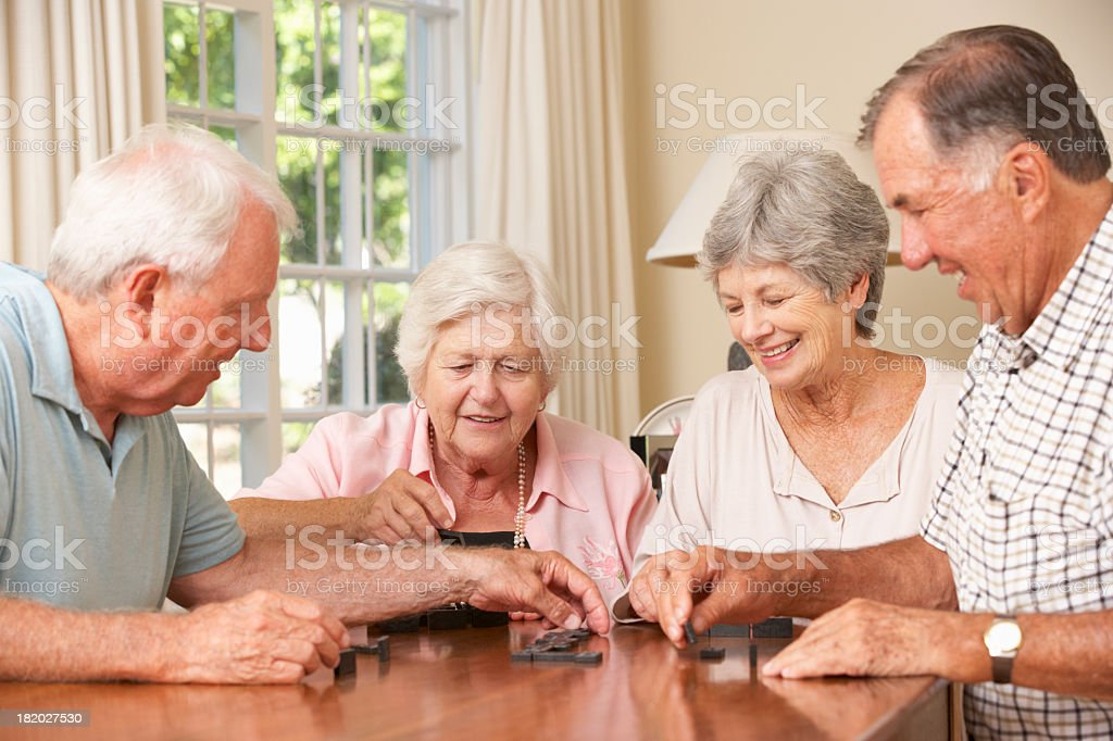 Group Of Senior Couples Enjoying Dominoes At Home stock photo