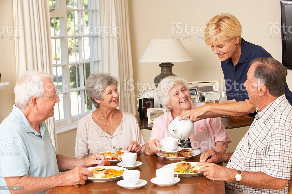 Group Of Senior Couples Enjoying Meal Together In Care Home stock photo