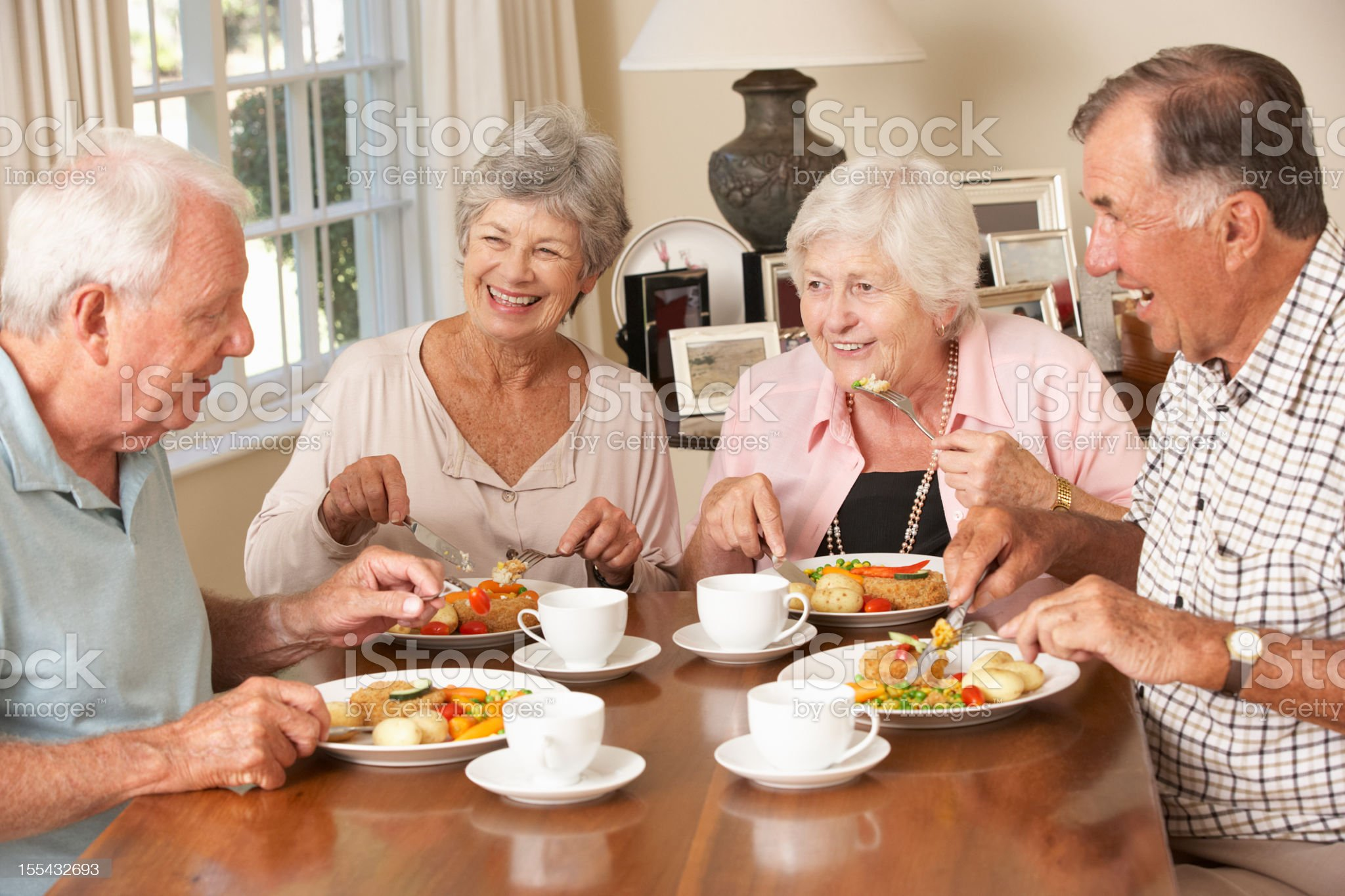 Group Of Senior Couples Enjoying Meal Together royalty-free stock photo